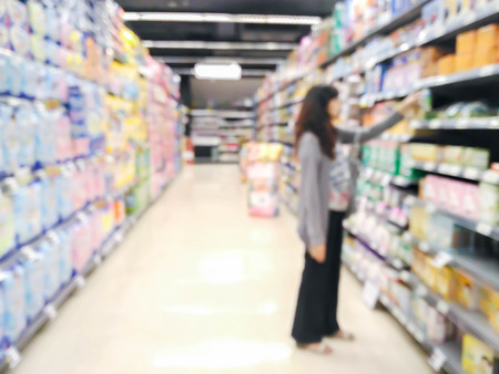 local supply: woman looking at supermarket shelf in blurry : for background use