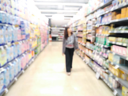 woman looking at supermarket shelf in blurry : for background use