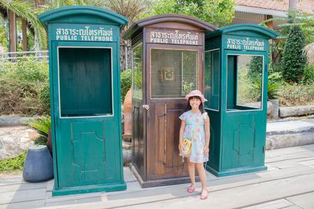 cabina telefonica: Muchacha asiática con el teléfono público retro