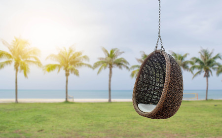 Rattan lounge hanging chair with white pillow with background of coconut palm tree on the beach