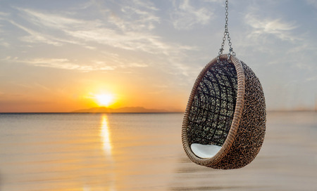 Rattan lounge hanging chair with white pillow near the beach with sunset Standard-Bild
