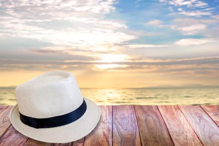 vintage woven hat on wood floor at the summer beach Stock Photo