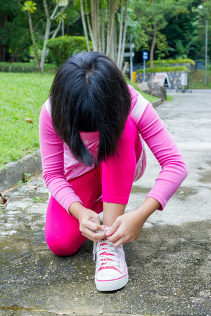 shoelace: girl in pink clothes tying her pink shoes
