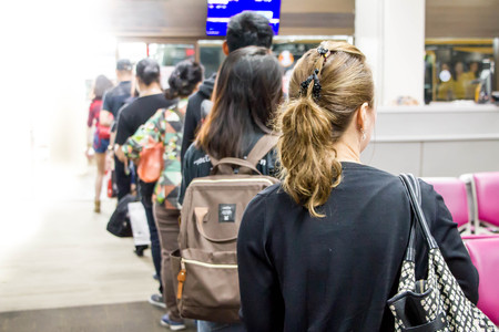 blurred of Asian passengers in the line queue at boarding gate of the airport