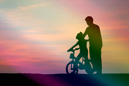 silhouette dad teach his daughter to bike on red sky background : Fathers Day concept