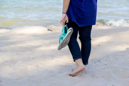 teenage girl walk with bare foot on the white sand and hold her shoes