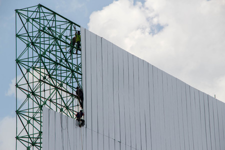 workers installing metal sheets on big billboard with background of blue sky and white cloud