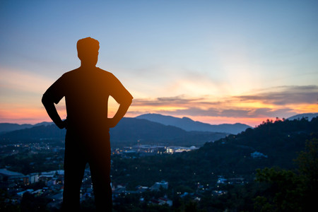 silhouette man stand on the top of mountain : concept of travel,success or  freedom