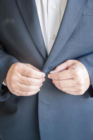 businessman buttoning his blue suit Stock Photo