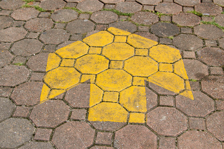 yellow arrow sign on grungy cement pavement Stock Photo