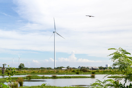 wind turbine in countryside landscape with blue sky and white cloud