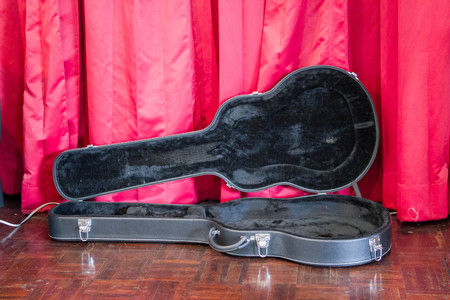 opened black guitar case on stage with background of red curtain