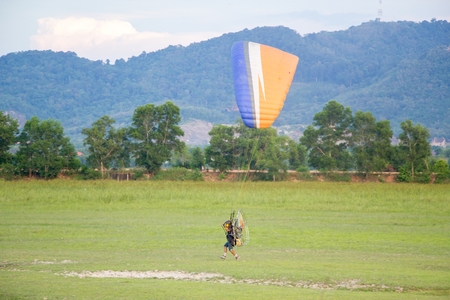 man with paramotor on green lawn prepare to fly up in the sky