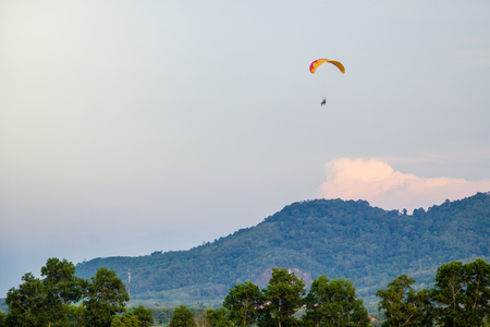 man with paramotor flying over mountain on blue sky background