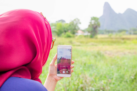 Muslim woman in red scarf (Hijab) look from back taking  photo of natural scene by smartphone 写真素材