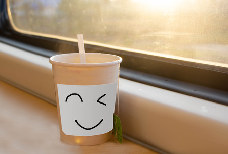 hot tea in paper cup on the table near window with sunlight