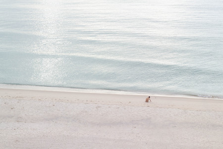 woman sitting alone on the beach and picking seashell