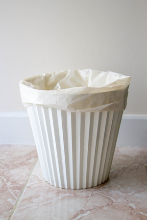 white plastic rubbish bin on the tile floor