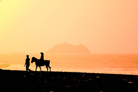 silhouette Dad walking with daughter riding on horse on the beach