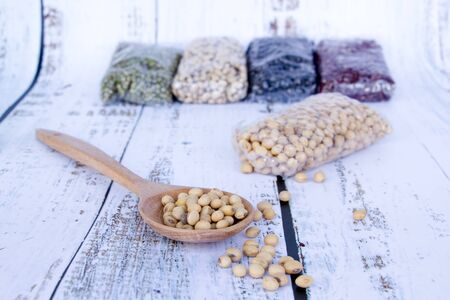 soy bean or soya bean in wood spoon on white wood floor with multicolor dried legumes for healthy on background