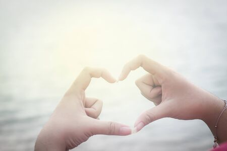 Girl hands in the form of heart on blue sky and water background with lens flare : concept of love, valentine 写真素材 - 125694873