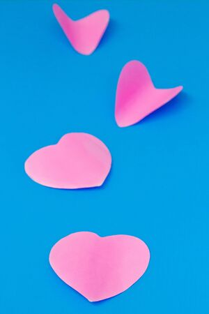 colored pink sheet of note paper, sticker note, note pad in heart shape Isolated on blue background 写真素材