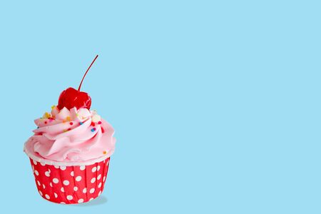cupcakes in red cup with buttercream and red cherry on top isolated on blue background 写真素材