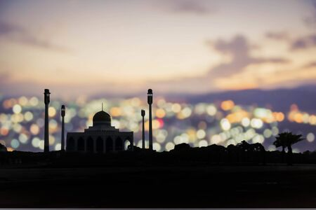 Ramadan Kareem :  Silhouette of Mosque (Masjid) on city  blur bokeh light