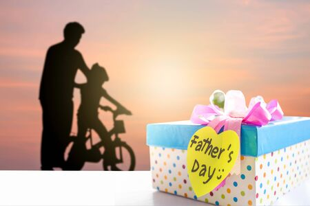 Fathers Day tag with gift box on the table with background of dad and child 写真素材