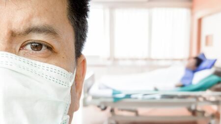 Closeup half face of a doctor wearing medical mask with blurred of patient on hospital bed background