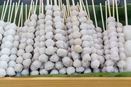 meat  ball on wood stick put on tray with banana leaf at street food Thai market