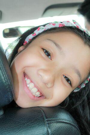 Happy cute Asian kid smilling in car 写真素材 - 128272869