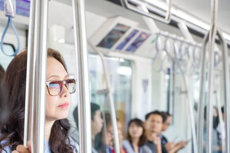 Asian woman with sunglasses standing in sky train with background of crowd people sitting on chair