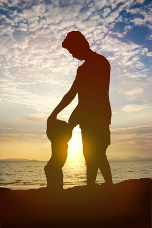 father and daughter playing together at the beach with sunset background