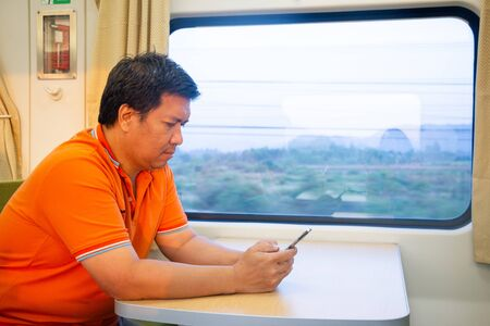 Asian man 40s sitting near the window and using smart phone on train to contact someone 写真素材