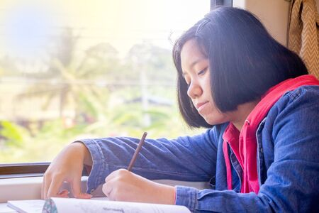 Asian teenager writing book or drawing picture on table inside railway