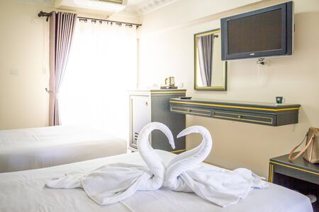 hotel housekeeper fold white towel as two swans or heart on bed