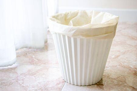 white plastic rubbish bin on the tile floor near the curtain in room 写真素材