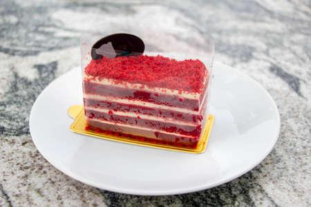 Red velvet cake and sliced black chocolate on white plate Imagens