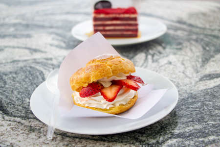 Choux cream, profiteroles with cream, and strawberry on white plate Imagens