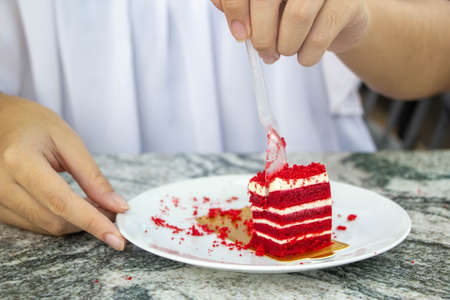 close up hand cutting red velvet cake with spoon in whiteplate