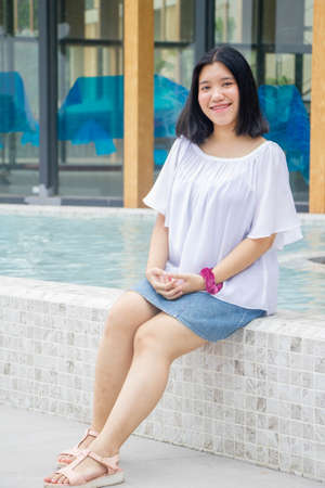 Asian teenager black hair with pink braces on teeth and red scrunchie on hand sitting on pool and smilling