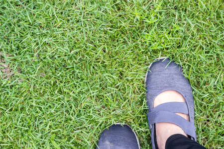 top view of woman feet in blue shoes on grass floor