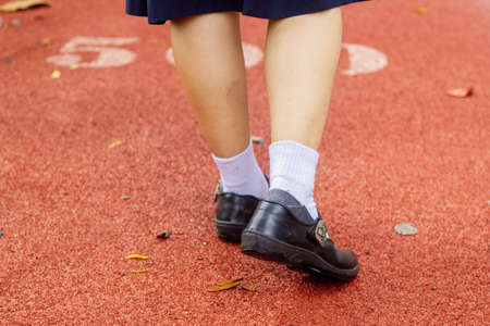 Thai girl student in uniform shoes look from back walking on red cement road with dried leaf
