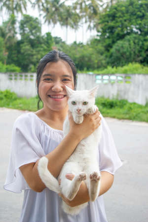 Asian teenager holding  white cat in her hands and smilling selective focus on cat Imagens