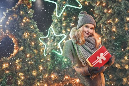 Girl holding gift box on winter festival. Celebrate New Year EVE. Against a background the Christmas lights. Фото со стока - 137761612