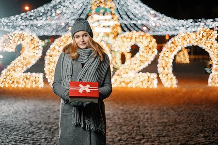 Girl holding gift box on winter festival. Celebrate New Year EVE 2020. Against a background the Christmas lights. Фото со стока