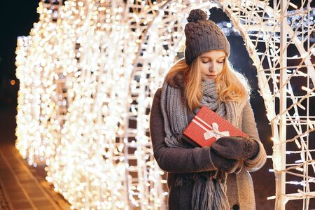 Girl holding gift box on winter festival. Celebrate New Year EVE. Against a background the Christmas lights.
