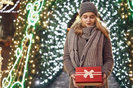Girl holding gift box on winter festival. Celebrate New Year EVE. Against a background the Christmas lights. Фото со стока - 137761622