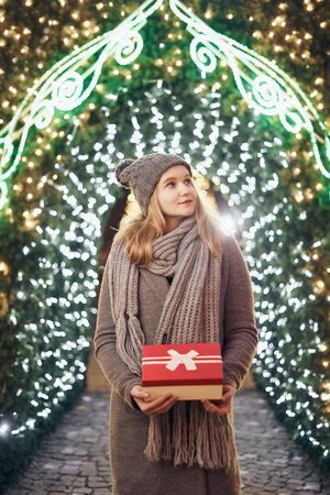 Girl holding gift box on winter festival. Celebrate New Year EVE. Against a background the Christmas lights. Фото со стока - 137761624